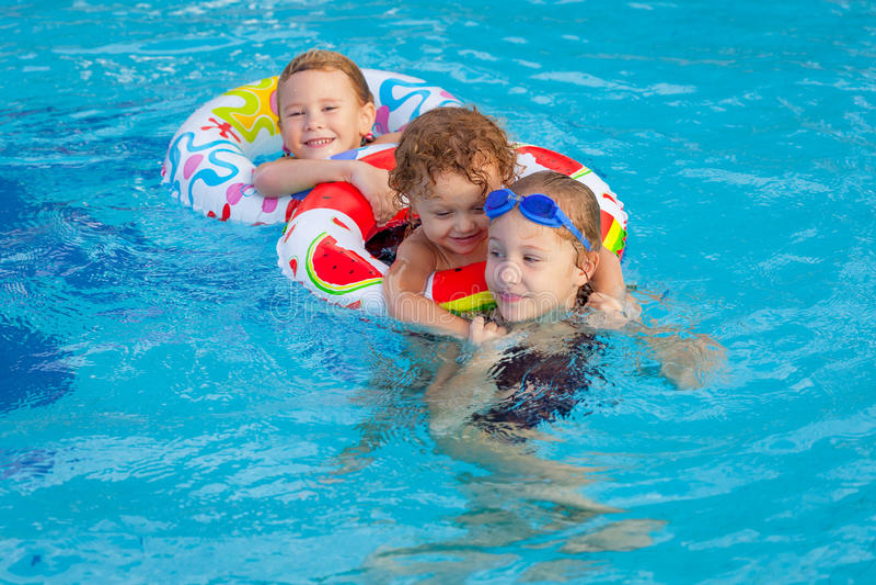 Glückliche kleine Kinder, die im Swimmingpool spielen stockbild