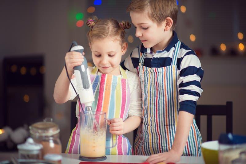 Glückliche kleine Kinder, die Weihnachtsplätzchen zubereiten stockfoto