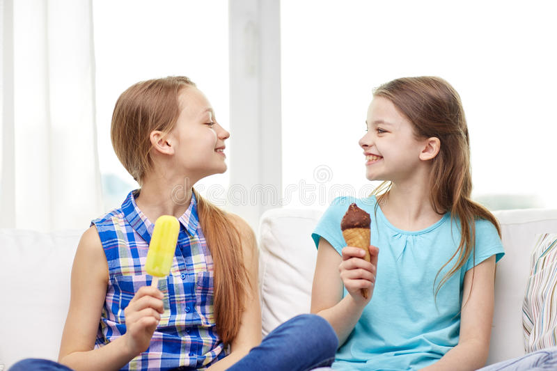 Glückliche kleine Mädchen, die zu Hause Eiscreme essen lizenzfreie stockfotografie