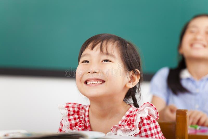 Glückliche kleine Mädchen im Klassenzimmer stockfoto