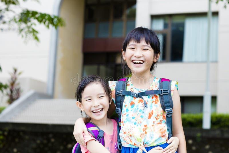 Glückliche kleine Mädchen mit den Mitschülern, die Spaß in der Schule haben lizenzfreie stockfotos