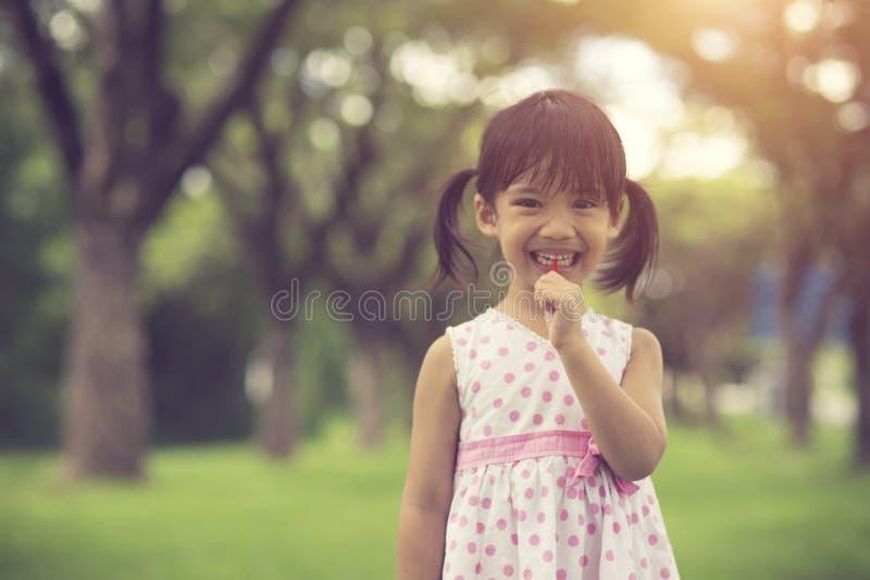 glückliche kleine Mädchen mit Lutschern draußen lizenzfreie stockfotos