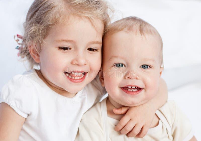 Glückliche kleine Schwester, die ihren Bruder umarmt stockbilder