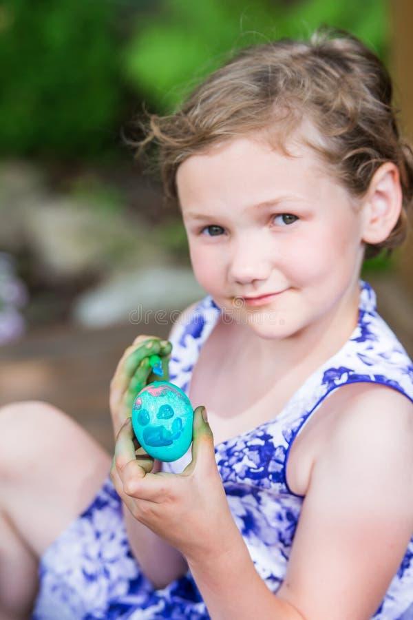 Glückliche kleines Mädchen-Haltungen mit gemaltem Osterei stockbild