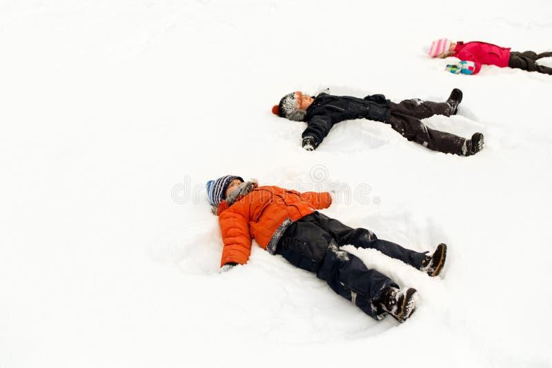 Glückliche Kleinkinder, die Schneeengel im Winter machen lizenzfreie stockbilder
