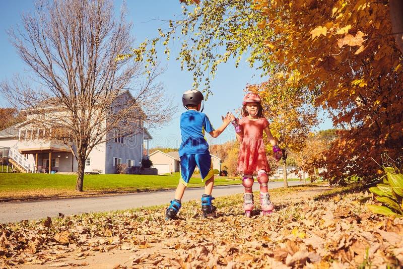 Glückliche Kleinkindrollschuhlaufen und Geben fünf stockbild