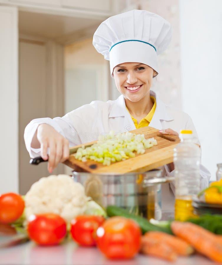 Glückliche Kochfrau, die vegetarisches Abendessen kocht stockfoto