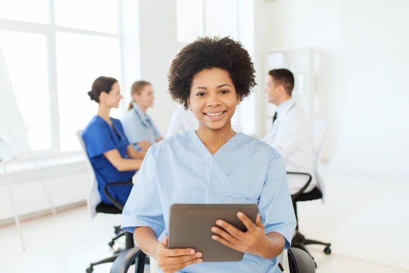 Glückliche Krankenschwester mit Tabletten-PC über Team am Krankenhaus stockbild