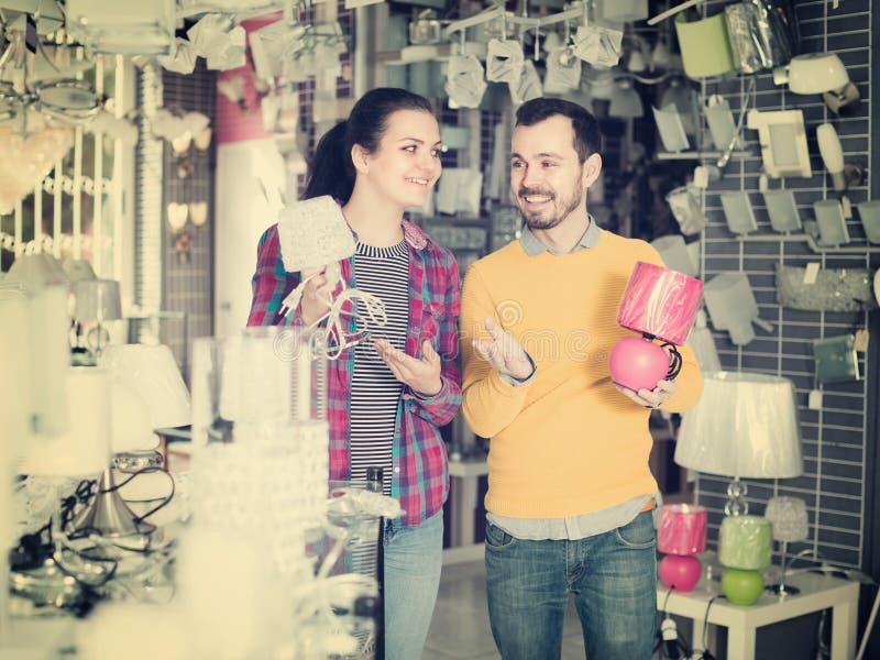 Glückliche Kunden im Shop von Haushaltsgeräten wählen Nachtla lizenzfreie stockbilder