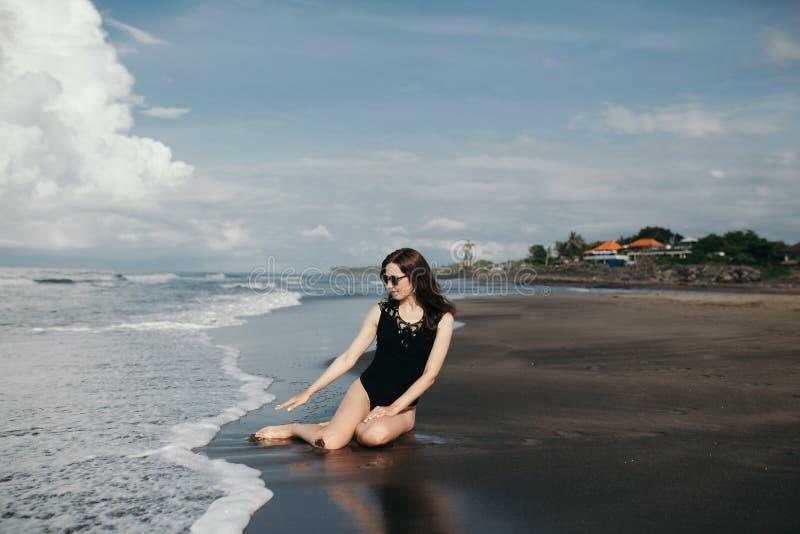 Glückliche Lächeln Brunette Frau, die mit Wellen in der schwarzen Badeanzug- und Denimjacke auf Ozeanhintergrund auf schwarzem Sa lizenzfreie stockfotos