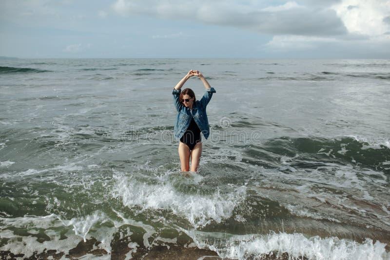 Glückliche Lächeln Brunette Frau, die schwarze Badeanzug- und Denimjacke am Ozeanhintergrund trägt, genießen, in Ozean, die Hände lizenzfreie stockfotografie
