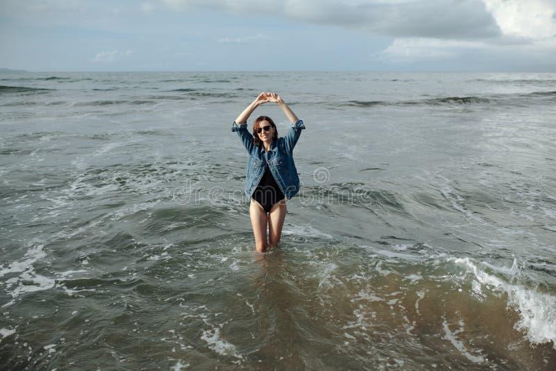 Glückliche Lächeln Brunette Frau, die schwarze Badeanzug- und Denimjacke am Ozeanhintergrund trägt, genießen, in Ozean, die Hände stockbilder