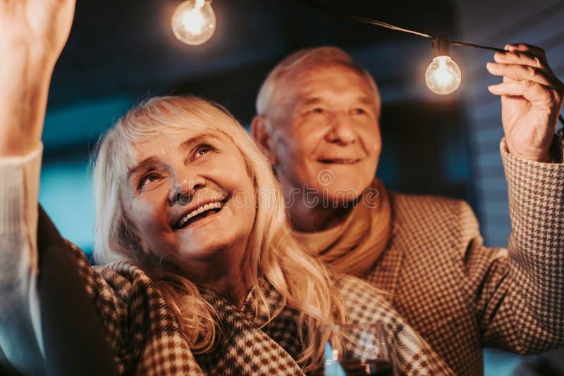 Glückliche lächelnde ältere Paare, die Girlande betrachten lizenzfreie stockfotografie