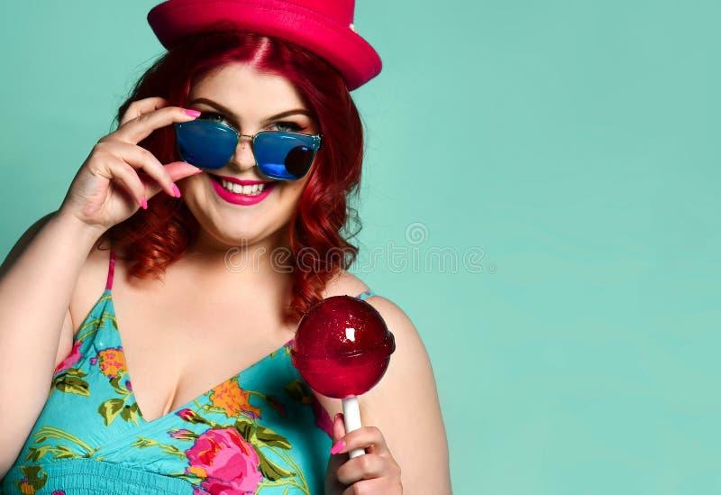 Glückliche lächelnde überladene fette mollige Frau im Hut und in der Sonnenbrille mit großem Extralutscher stockfotos