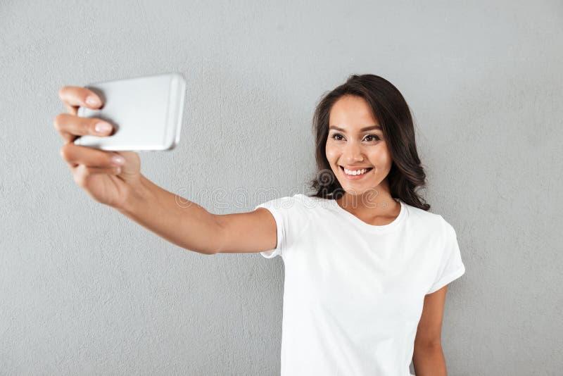 Glückliche lächelnde asiatische Frau, die selfie nimmt stockfotos