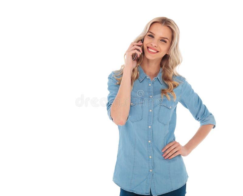 Glückliche lächelnde blonde zufällige Frau, die am Telefon spricht lizenzfreies stockbild