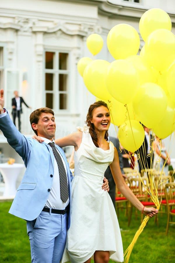 Glückliche lächelnde Braut und Bräutigam, die gelben Ballonhintergrund hält stockbilder