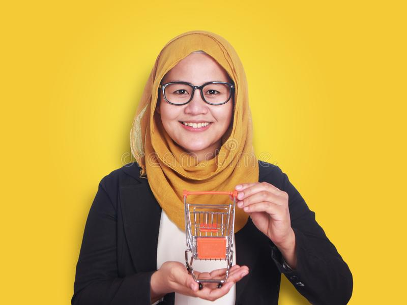 Glückliche lächelnde erfolgreiche asiatische moslemische Frau, die Minieinkaufslaufkatze auf ihrer Hand, on-line-E-Commerce-Marke stockfoto