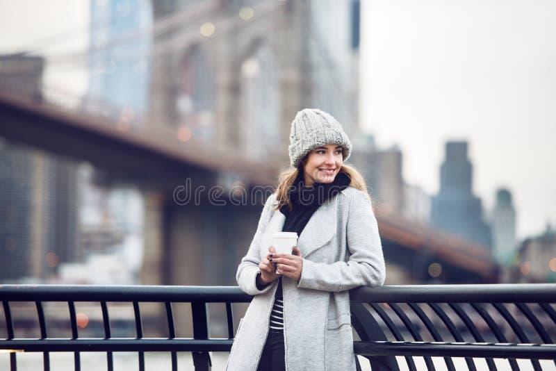 Glückliche lächelnde erwachsene touristische Frau, die Papierkaffeetasse hält und die New- York Cityansicht genießt stockbild