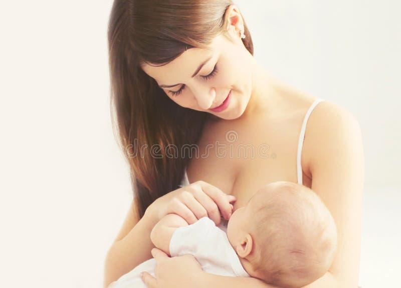 Glückliche lächelnde Fütterungsbrust der Mutter des Porträts ihr Baby zu Hause stockfotos