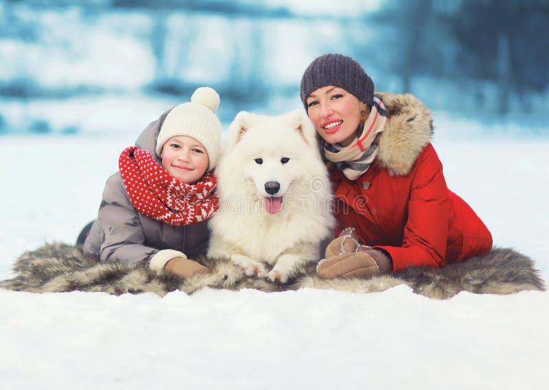 Glückliche lächelnde Familie, Mutter und Sohn, die mit weißem Samoyedhund im Winter geht lizenzfreies stockbild