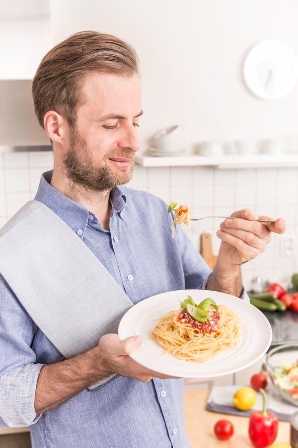 Glückliche lächelnde Fleisch fressende Spaghettis Bewohner von Bolognese in der Küche stockfotografie