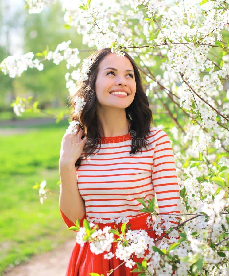 Glückliche lächelnde Frau in blühendem Frühlingsgarten lizenzfreies stockfoto