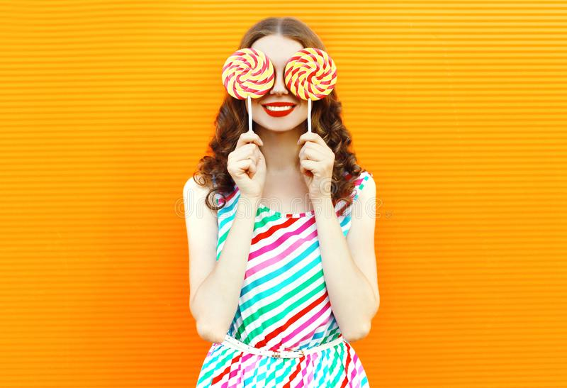 Glückliche lächelnde Frau des Porträts, die ihre Augen mit Lutscher zwei im bunten gestreiften Kleid auf orange Wand versteckt stockfotos