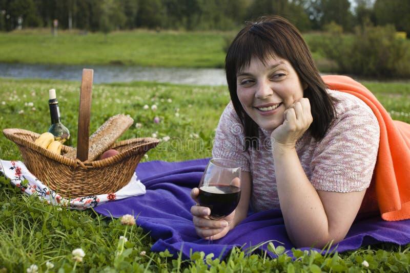 Glückliche lächelnde Frau des reifen Brunette mit Glas Wein auf dem Picknick, das Spaß, wirkliches modernes Leutekonzept des Lebe stockbilder