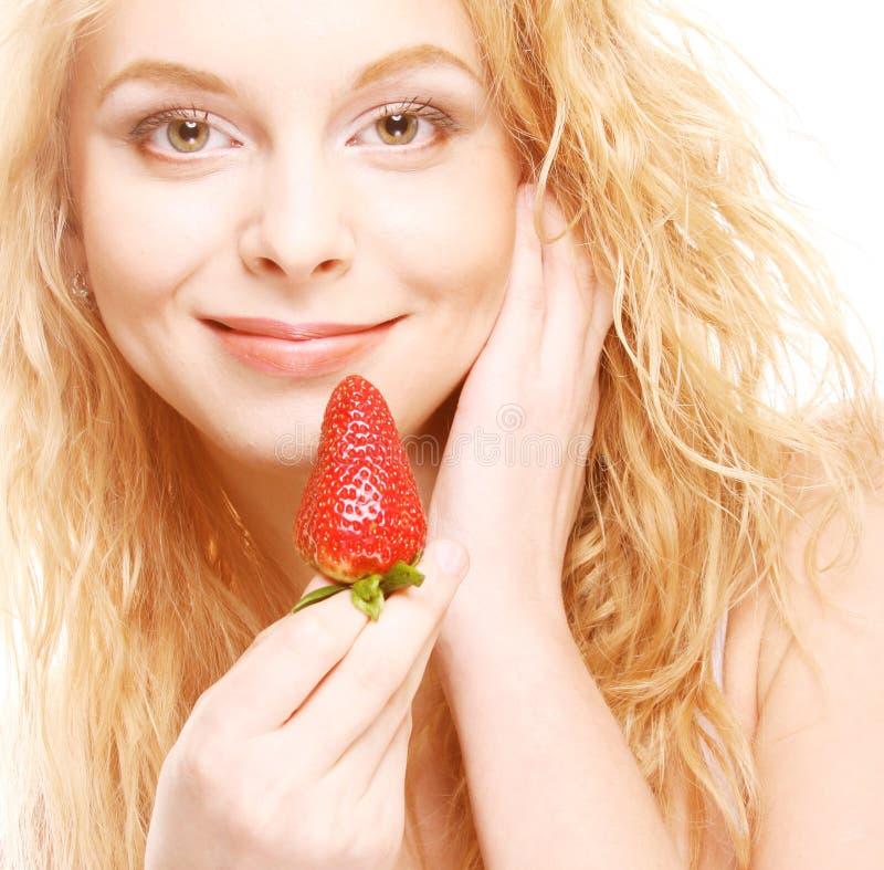 Glückliche lächelnde Frau mit Erdbeere lizenzfreie stockfotos