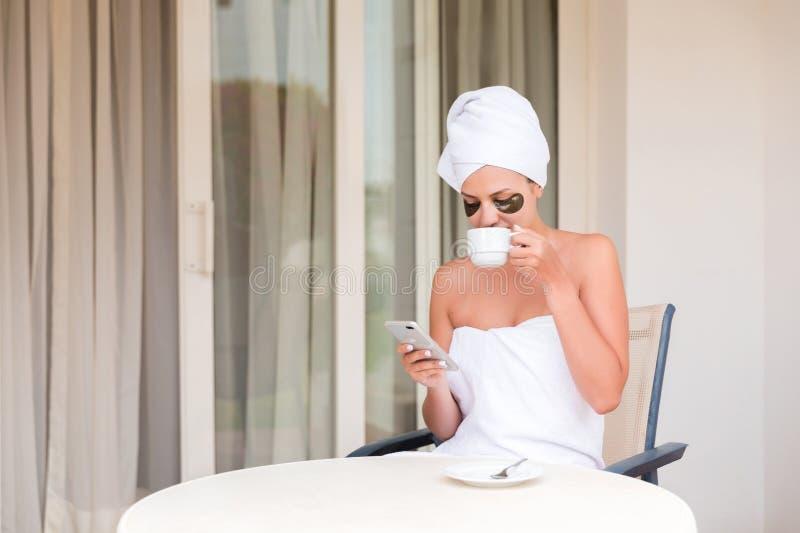 Glückliche lächelnde Frau in Unteraugenflecken readind sms Mitteilung und trinkender Kaffee am Hotelterrassenerholungsort Morgenf lizenzfreie stockfotografie