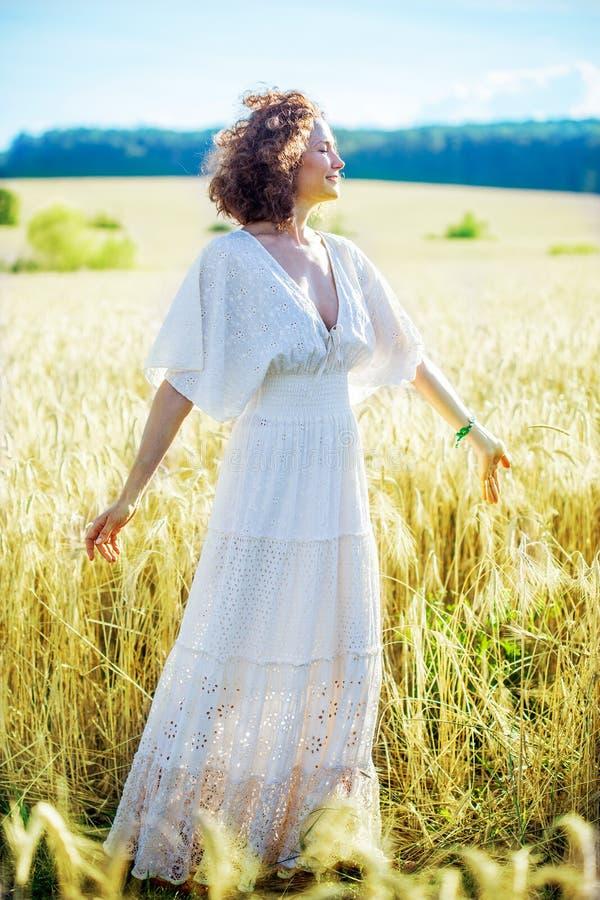 Glückliche lächelnde Frau von mittlerem Alter, die in ein weißes Kleid in einem f spinnt stockfotos