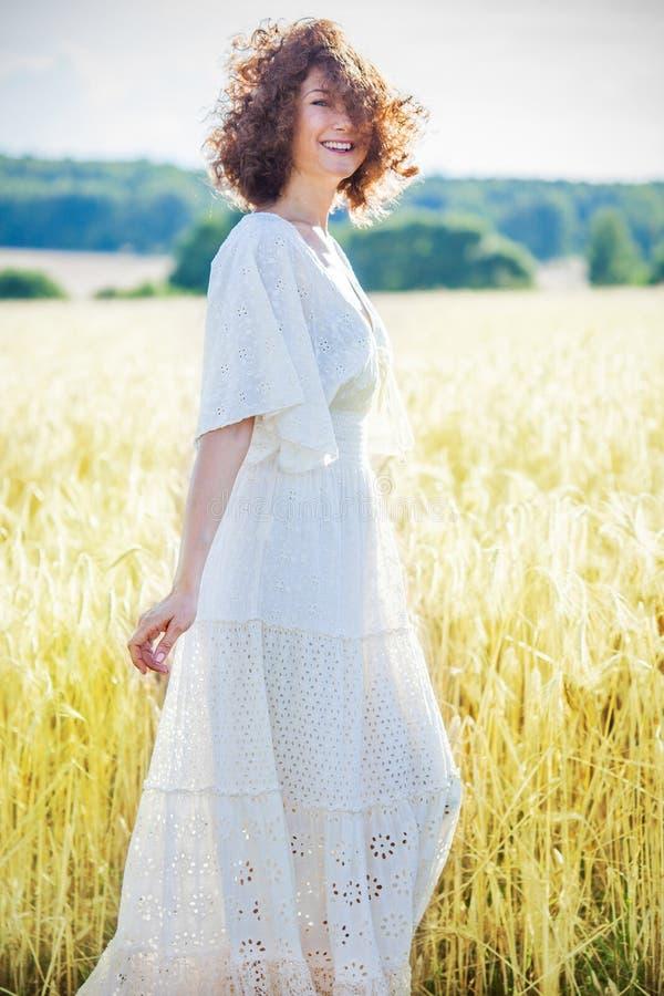 Glückliche lächelnde Frau von mittlerem Alter in einem weißen Sommerkleid auf einem Gebiet unter den Kornähren Mode, Art lizenzfreie stockbilder