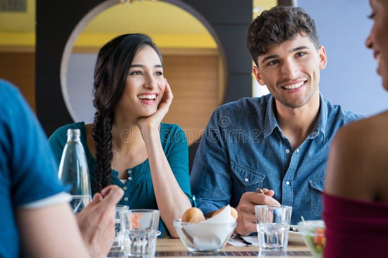 Glückliche lächelnde Freunde, die zu Mittag essen stockfotografie