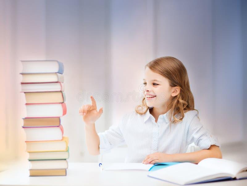 Glückliche lächelnde gebundene Bücher des Studentenmädchens stockbilder