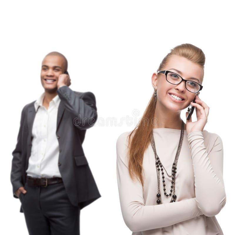 Glückliche lächelnde Geschäftsleute, die per Mobiltelefon nennen lizenzfreies stockfoto