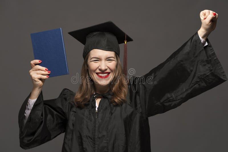 Gl?ckliche l?chelnde graduierte Studentin mit Stoppel in den Brillen, die schwarzen Umhang und Doktorhut tragen stockfoto
