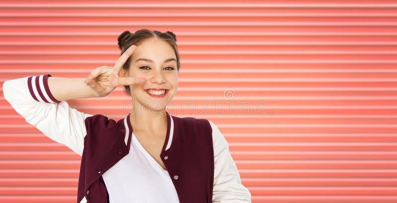 Glückliche lächelnde Jugendliche, die Friedenszeichen zeigt lizenzfreie stockfotos