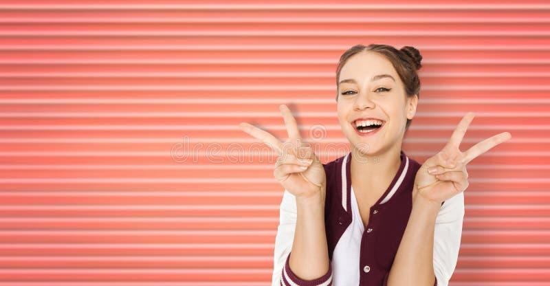 Glückliche lächelnde Jugendliche, die Friedenszeichen zeigt stockfotos