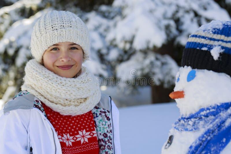 Glückliche lächelnde Jugendliche, die mit einem Schneemann auf einem schneebedeckten Gewinn spielt lizenzfreie stockfotografie