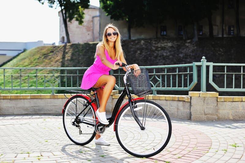 Glückliche lächelnde junge Frau auf einem Fahrrad im Sommer stockbilder