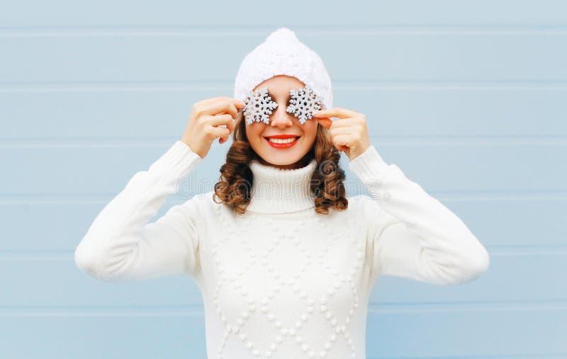 Glückliche lächelnde junge Frau in der Strickmütze und in der Strickjacke mit Schneeflocken auf einem Gesicht, das Spaß über blau stockbilder