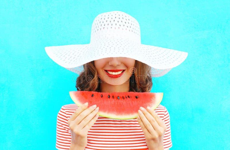 Glückliche lächelnde junge Frau des Modeporträts hält eine Scheibe der Wassermelone in einem Strohhut lizenzfreies stockbild