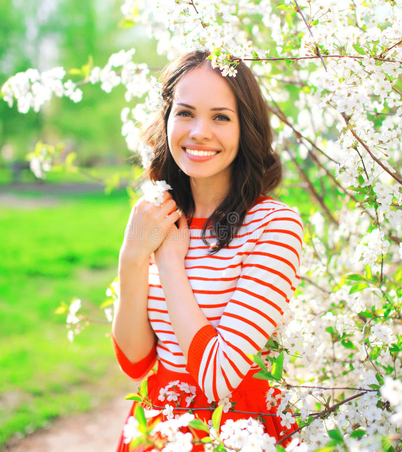 Glückliche lächelnde junge Frau des Porträts in Frühling blüht stockbild
