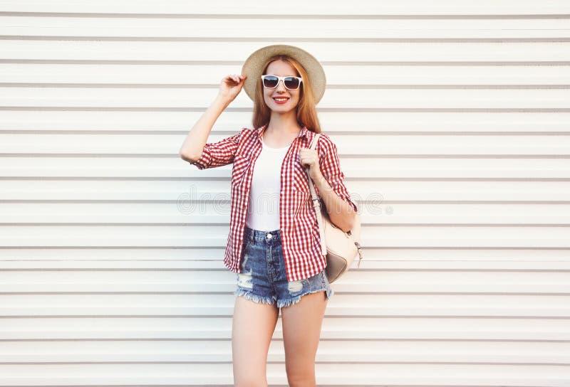 Glückliche lächelnde junge Frau im Sommerrundenstrohhut, kariertes Hemd, kurze Hosen, die auf weißer Wand aufwerfen stockfotografie