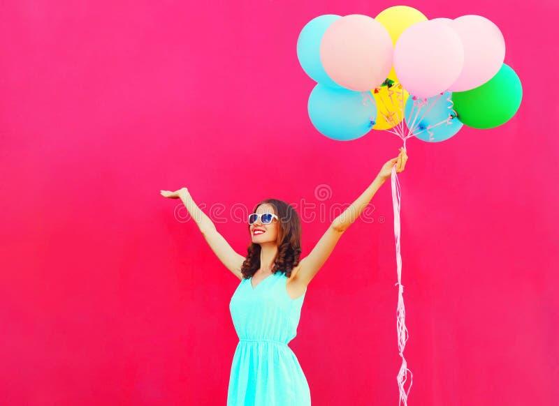 Glückliche lächelnde junge Frau mit bunten Ballonen einer Luft hat Spaß im Sommer über einem rosa Hintergrund lizenzfreie stockfotografie
