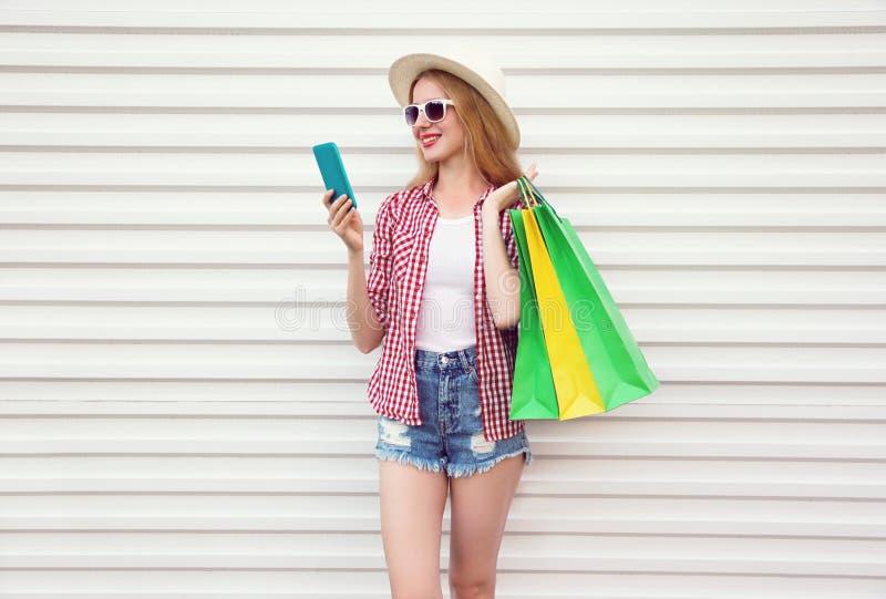 Glückliche lächelnde junge Frau mit dem Telefon, bunte Einkaufstaschen im Sommerrundenstrohhut halten, kariertes Hemd, kurze Hose lizenzfreies stockfoto