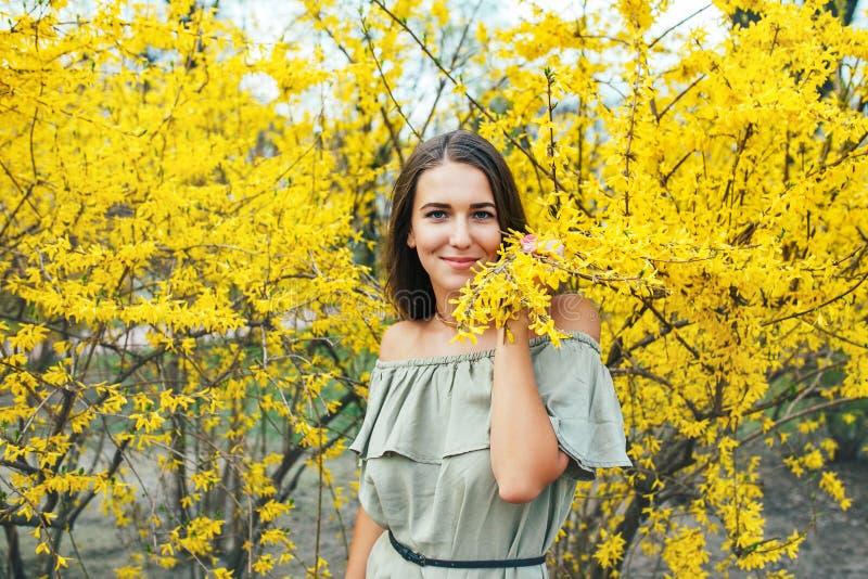 Glückliche lächelnde junge Frau mit Frühling blüht am Garten lizenzfreie stockbilder