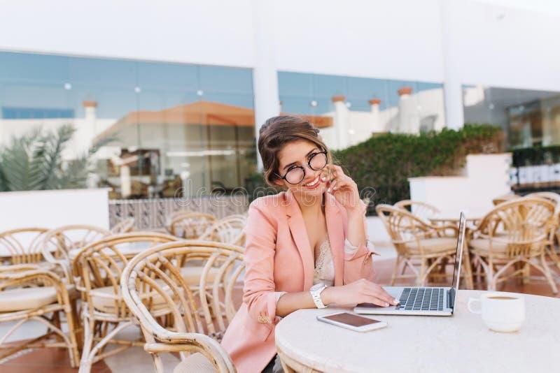 Glückliche, lächelnde junge Frau mit Laptop im Straßencafé, Arbeit über Computer draußen genießend und trinken Kaffee Tragen inte stockfoto