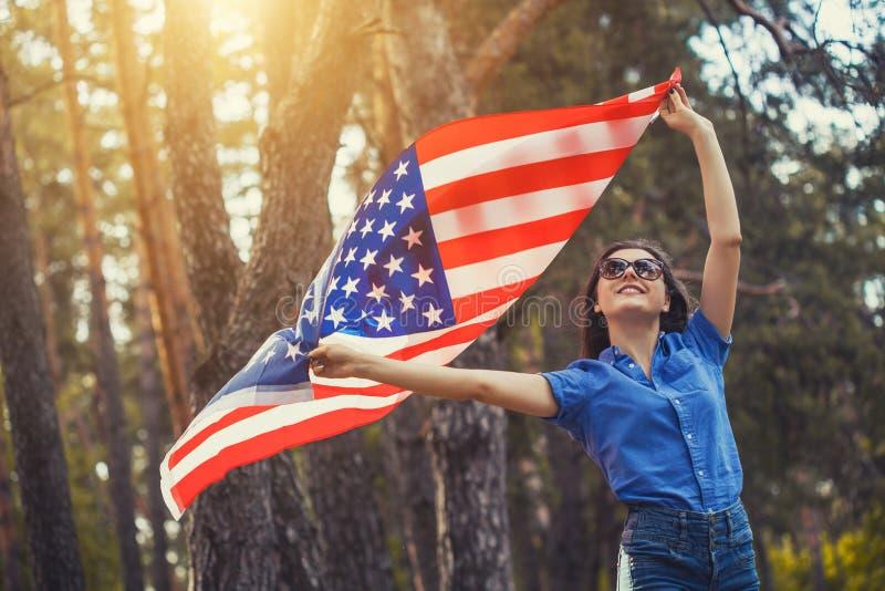 Glückliche lächelnde junge Frau mit nationaler amerikanischer Flagge draußen lizenzfreie stockfotos